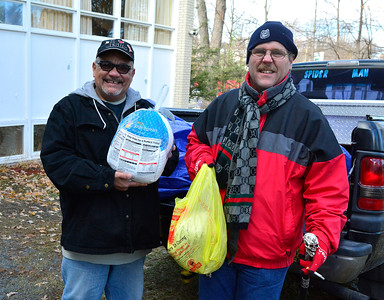 "11/22/2016 Mike Orazzi | Staff Chaplain Jose Luis Delgado and Mark Lozier hold turkeys while distributing them at ""Meals for the Needy"" at Zion Lutheran Church Tuesday morning."