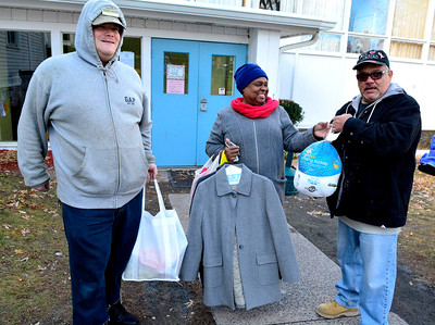 "11/22/2016 Mike Orazzi | Staff Denise Allen (center) leaves the Zion ""Meals for the Needy"" with a Thanksgiving Day meal and some new coats at Zion Lutheran Church Tuesday morning. On the left is Toby Nygren and on the right is Chaplain Jose Luis Delgado.  Nearly 300 meals will be distributed to area needy this week alone."