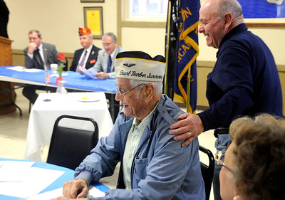 12/7/2011 Mike Orazzi | Staff World War II veteran and Pearl Harbor survivor Ed Riccio Jr. gets a pat on the shoulder from Gene Minella at the Pearl Harbor Day ceremony at American Legion in Bristol on Wednesday morning, December 7, 2011.