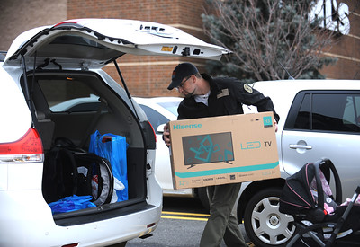 11/25/2016 Mike Orazzi | Staff Chris Staggers loads an LED TV into his vehicle while Black Friday shopping with this wife Aimee and their one-week-old daughter Aubree at the Kohl's in Plainville Friday.