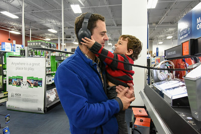 112416  Wesley Bunnell | Staff  Alejandro Barrios of Avon entertains his 11/2 year old son Christian as his wife and family shop in the electronics section of Best Buy on Black Friday.