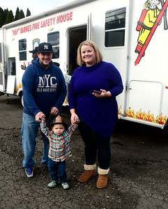 "11/26/2016 Mike Orazzi | Staff Jason and Jennifer Miranda with their son Jaxon after getting a tour of the ""Hap"" Barnes Fire Safety House during the Kids' Carnival held at the New England Carousel Museum Saturday."