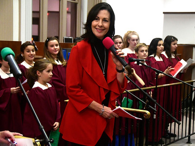 11/29/2016 Mike Orazzi | Staff Mary Lynn Gagnon leads the St. Joseph Church Children & Youth Choir during the 65th Annual Bristol Carol Sing and the 26th Annual Holiday Lighting Ceremony held inside Webster Bank on Main Street Tuesday night.