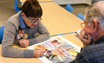 112916  Wesley Bunnell | Staff  Instructor June Webster, shown left,  goes over the days painting with Tom Anderson of Wethersfield in the adult watercolor class at the New Britain Museum of American Art on Tuesday afternoon.