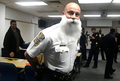 "11/29/2016 Mike Orazzi | Staff Bristol Police Chief Brian Gould wearing a fake white beard before presenting a check to the American Cancer Society's Lynn Kipphut for $3,760 check from members of the Bristol Police Department as part of the ""No Shave November"" on Tuesday."