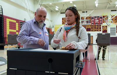 110816  Wesley Bunnell   Staff  Tabulator Tender Mike Bracken, shown left, helps Alexis Calarco with entering her ballot into the voting machine at New Britain High School during Tuesday's elections.