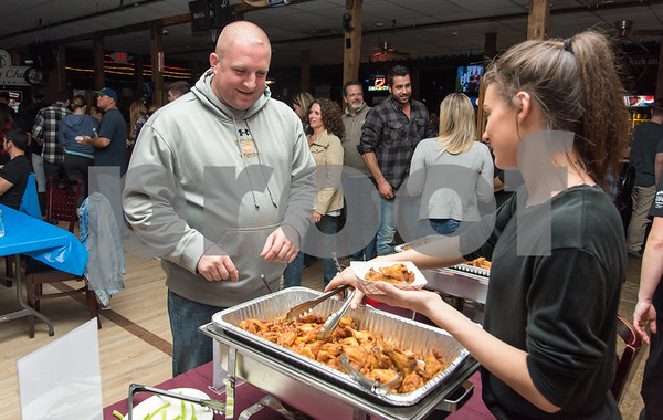 11/6/17 Wesley Bunnell | Staff The Southington Chamber of Commerce held their 12th annual Wing Fest on Monday evening at The Cadillac Ranch. Jamie Yakushewich of Seymour, L, samples wings from Cadillac Ranch server Liza Bartolotta.