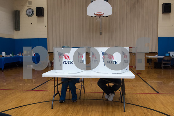 11/7/17 Wesley Bunnell | Staff The Griswold School polling location was busy throughout the day Tuesday. Voters sit at a table casting their ballots.