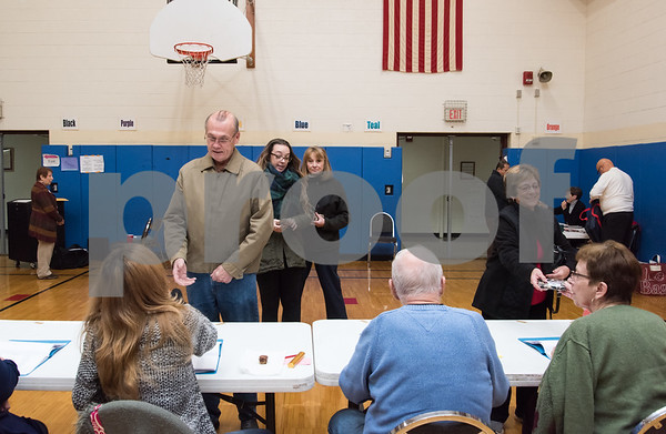 11/7/17 Wesley Bunnell | Staff The Griswold School polling location was busy throughout the day Tuesday. John McCloskey checks in at the table to receive his ballot while daughter Courtney and wife Colleen wait behind him.