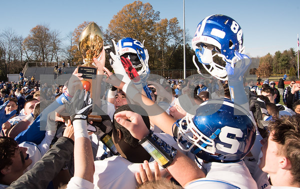 11/23/17 Wesley Bunnell | Staff Southington football topped Cheshire on Thanksgiving morning in the Apple Valley Classic at Cheshire High School. Players hoist their helmets and trophy.