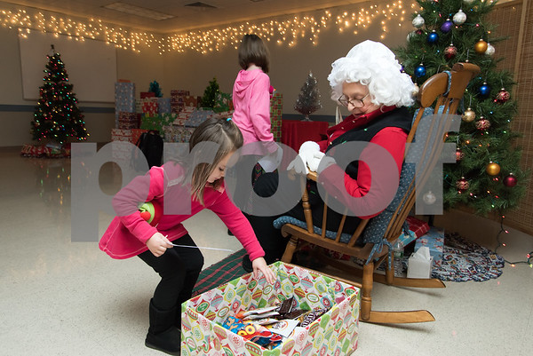 11/27/17 Wesley Bunnell | Staff Santa and Mrs. Claus visited the Berlin Recreation Center on Monday evening as guests from Berlin Parks & Recreation. Ava Kelly picks out a snack from Mrs. Claus as sister Mya Kelly finishes up talking to Santa.