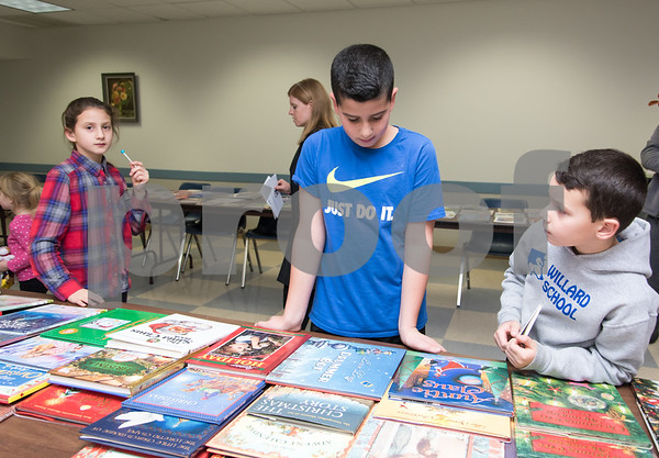 11/27/17 Wesley Bunnell | Staff Santa and Mrs. Claus visited the Berlin Recreation Center on Monday evening as guests from Berlin Parks & Recreation. Liliana, age 9, Danny, age 10, and Joseph Bellini pick out books after visiting Santa.