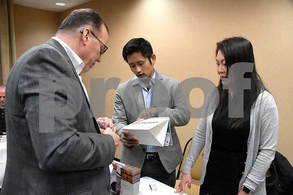 11/29/2017 Mike Orazzi | Staff John Rivers talks with Dr. Richard Sui and Dr. Julie Sheen of Eye Life Vision Center during the Southington Chamber of Commerce New Member Showcase held at Comfort Suites Southington Wednesday evening.