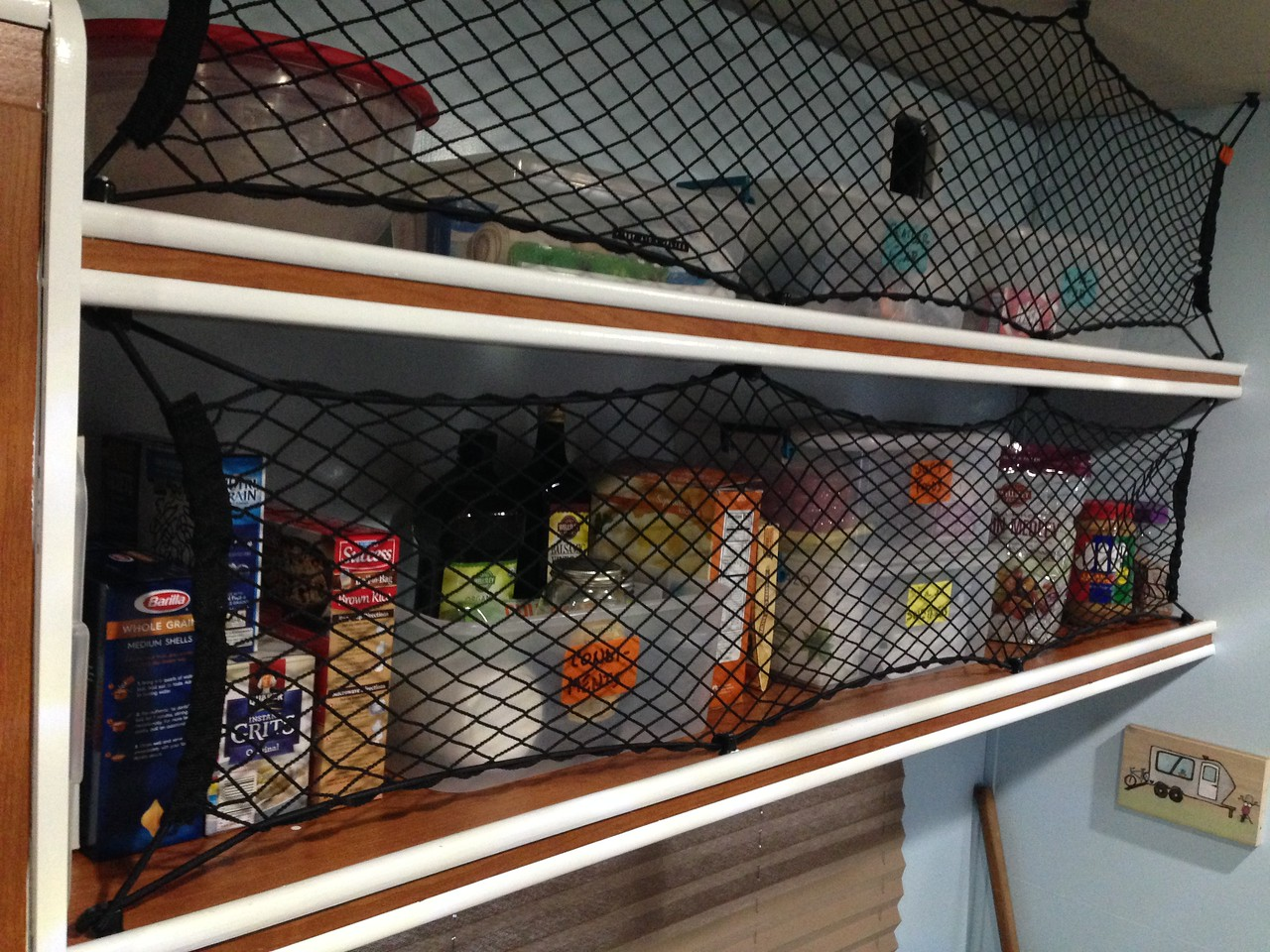 Groceries that don't go in the fridge are kept behind these bungee cargo nets.