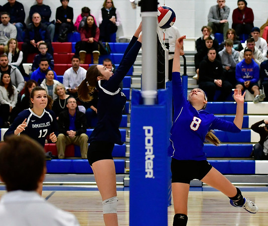11/7/2018 Mike Orazzi | Staff St. Paul Catholic High School's Alexis Carabetta (8) and Immaculate's Finan Deakin (19) during the Class S Second Round Girls Volleyball Tournament in Bristol Wednesday night.