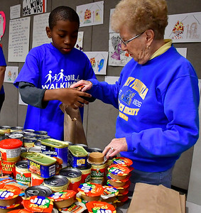 11/13/2018 Mike Orazzi | Staff Volunteers Malachi Gordon,10 and Hilda Schuass while at St. Andrew Lutheran Church as they fill bags with donated food for area homeless on Tuesday night in Bristol.