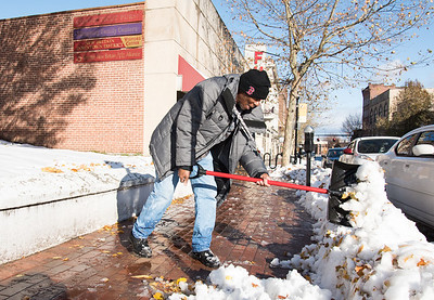 11/16/18  Wesley Bunnell | Staff  Sam Timmons from the YMCA helps clean up the sidewalk near West Main St and High St on Friday afternoon following the first winter storm of the season which lasted from last Thursday until Friday morning.