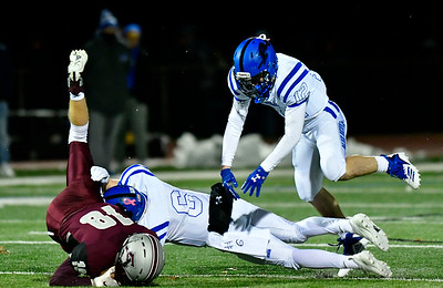 11/211/21/2018 Mike Orazzi | Staff Plainville's Christian Collin (6) and Tanner Callahan (12) with Farmington's Mitchell Guglielmo (18) during Wednesday night's football game at Farmington High School.