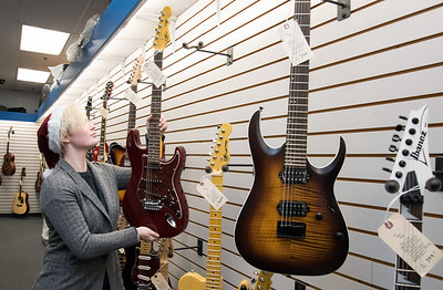 11/21/18  Wesley Bunnell | Staff  Em Castellano of The Music Shop in Southington hangs an electric guitar for sale in anticipation of the upcoming kickoff to holiday sales on Wednesday afternoon.
