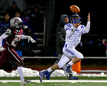 11/21/2018 Mike Orazzi | Staff Plainville's Brady Callahan (22) and Farmington's Clyde Wiafe (24) during Wednesday night's football game at Farmington High School.