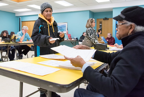 11/06/18 Wesley Bunnell | Staff Marcia Santos prepares to receive her ballot from Ballot Clerk Bessie Surratt at the New Britain Senior Center Polling Location on Pearl St on Tuesday afternoon.