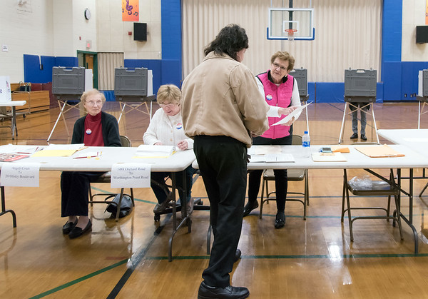 11/06/18 Wesley Bunnell | Staff A voter at Willard Elementary School's voting location is handed his ballot by Ballot Clerk Judith D'Onofrio on Tuesday night after being helped by checker's Irene Fiori, L, and Elaine Borselle.