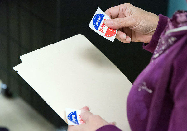 11/06/18 Wesley Bunnell | Staff The Tabulation Tender prepares to hand out an I Voted sticker to a voter on Tuesday afternoon at the New Britain Senior Center Polling Location on Pearl St.