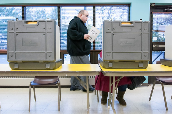 11/06/18 Wesley Bunnell | Staff Adrian Centeno walks to the tabulation machine after filling out his ballot on Tuesday afternoon at the New Britain Senior Center Polling Location on Pearl St.