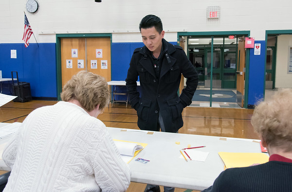 11/06/18 Wesley Bunnell | Staff Thanh Nguyen is helped by checker Elaine Borselle at the Willard Elementary School voting location on Tuesday night.
