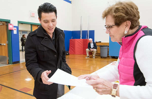 11/06/18 Wesley Bunnell | Staff Thanh Nguyen is handed his voting ballot by Ballot Clerk Judith D'Onofrio at the Willard Elementary School voting location on Tuesday night.