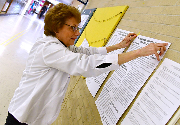 11/6/2018 Mike Orazzi | Staff Addie Monteleone tapes a ballot question to a wall at the Edgewood School in Bristol Tuesday afternoon.