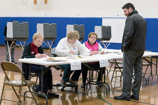 11/06/18 Wesley Bunnell | Staff Daniel Fortuna, R, is greeted by checkers Irene Fiori and Elaine Borselle prior to receiving his ballot from Ballot Clerk Judith D'Onofrio at the Willard Elementary School on Tuesday night.