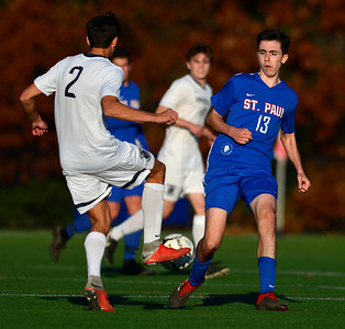 11/8/2018 Mike Orazzi | Staff Immaculate High School's (2) not on the roster and St. Paul Catholic High School's William Barton (13) during the Class S Second Round Boys Soccer Tournament held at the Farmington Sports Arena Thursday.