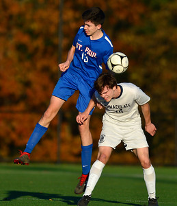 11/8/2018 Mike Orazzi | Staff St. Paul Catholic High School's William Barton (13) and Immaculate High School's Quinn Guth (14) during the Class S Second Round Boys Soccer Tournament held at the Farmington Sports Arena Thursday.