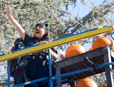 Official pumpkin dropper Cindy Olvera waves to the crowd before being lifted up on a crane during the annual pumpkin drop at Chico State on Thursday in Chico. (Matt Bates -- Enterprise-Record)