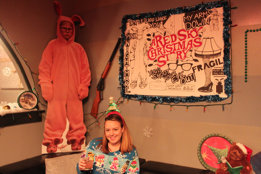 A girl in a Christmas sweater holds a drink in front of a cardboard cutout of a character from A Christmas story