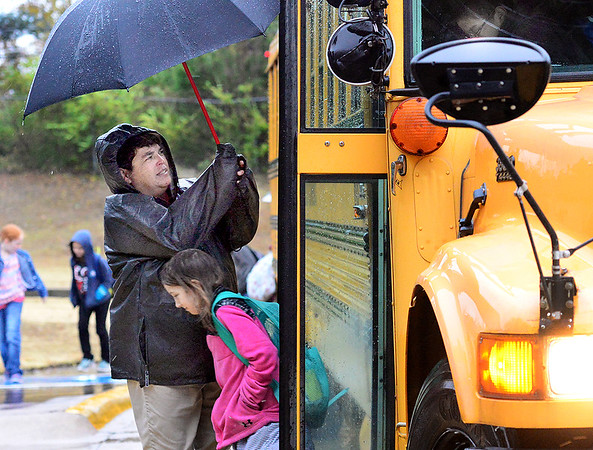 KEVIN HARVISON | Staff photo<br /> Angela Cooley holds and umbrella for Murraya Hancock as she and other students exit a MPS bus Thursday morning in a cold rain.
