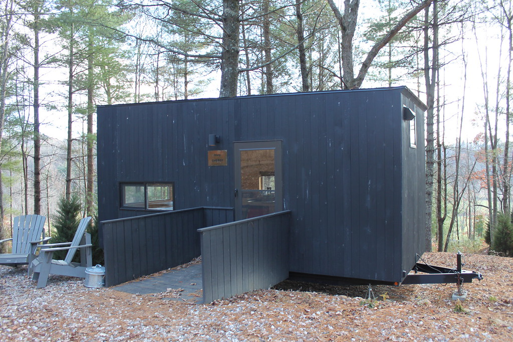 A black wooden tiny house sits in the forest with two Adirondack chairs