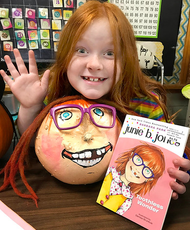KEVIN HARVISON | Staff photo<br /> Cali Farris poses with her pumpkin in Christie Short's Emerson Second Grade Class. The class had to decorate a pumpkin from the character of a book. Farris chose Junie B. Jones.