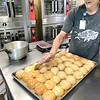 KEVIN HARVISON | Staff photo<br /> Claudia Travis butters some rolls in preparation for Will Rogers students lunch.