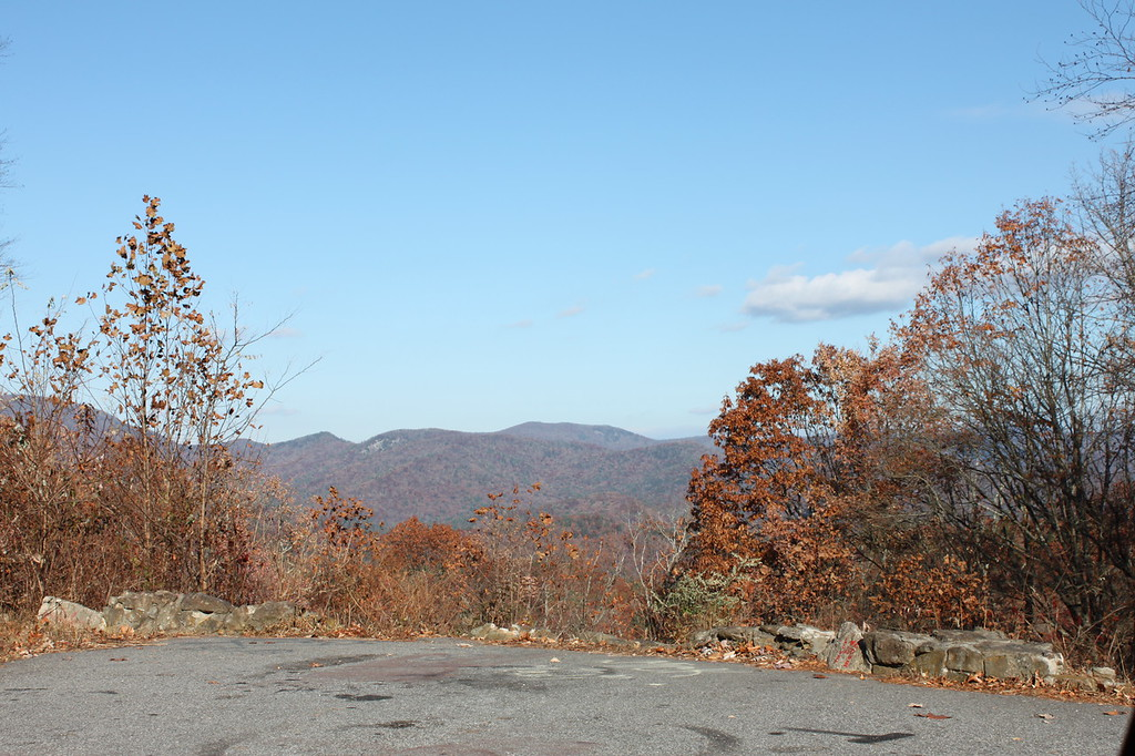 An overlook shows fall leaves and mountains