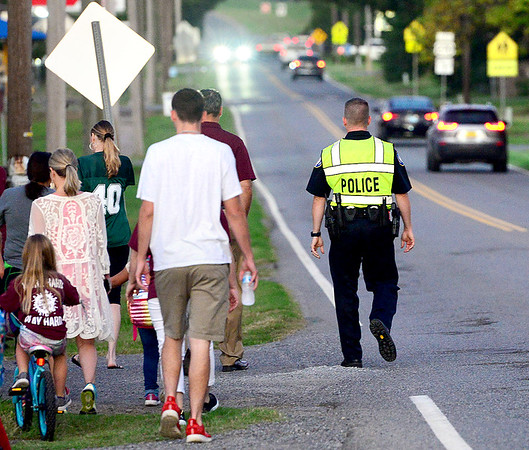 KEVIN HARVISON | Staff photo<br /> A Krebs Police Officer watches for cars near the end of the line, as a group from Krebs participate in the national Walk and Bike to School event.