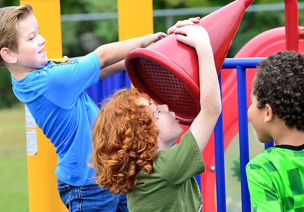 KEVIN HARVISON | Staff photo<br /> Pictured from left, Chevy Lane Cooper, Levi Lightle and Raphiah Conway take turns playing on the playground speaker at Chadick Park.