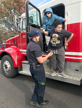 KEVIN HARVISON | Staff photo<br /> McAlester Firefighter Josh Parker, left, helps Zane Thurman, top blue and Teagan Chinaka, right, out of the cab of a McAlester Fire Truck after the MFD Fire Safety assembly.