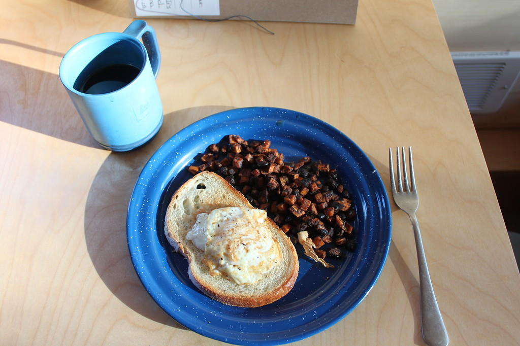 A blue plate holds breakfast of a fried egg on toast with a sweet potato hash, alongside a fork and blue mug of coffee