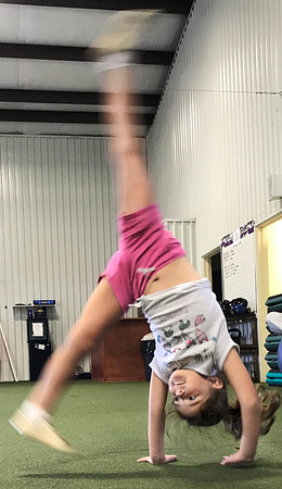 KEVIN HARVISON   Staff photo<br /> Brooklyn Evans does a series of cartwheels during a break between workouts in the after school program at Signature Fitness.