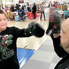 KEVIN HARVISON | Staff photo<br /> TJ Ketchers, left, gets some boxing tips from Luke Hurst of Breaking Limits Mixed Martial Arts Academy Saturday during the Santas Helper Fair.