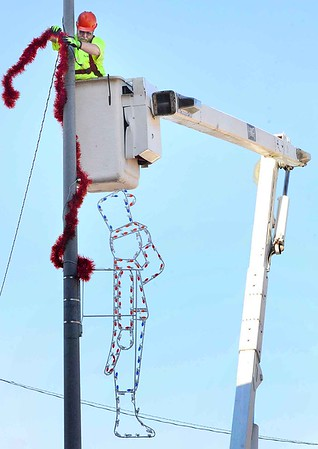 KEVIN HARVISON | Staff photo<br /> City of McAlester employee Clifford Harrison works to put up Christmas decorations on Carl Albert Parkway.