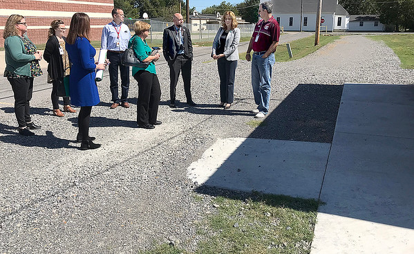 KEVIN HARVISON | Staff photo<br /> Krebs Public School Superintendant Patrick Turner, far right, shows off the new 1/4 mile walking track around the KPS baseball field during a visit from TSET officals. TSET money was used to make the track for the school as well as use by the community. Future plans call for the track to be paved.
