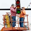 KEVIN HARVISON | Staff photo<br /> Built Right Construction workers remove a traffic light on Main Street and Choctaw Avenue Wednesday.